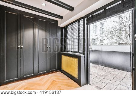 Corridor Of Contemporary Apartment With Black Closets And Opened Doorway Leading To Terrace