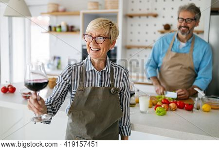 Senior Couple Having Fun, Cooking And Drinking Wine In Home Kitchen