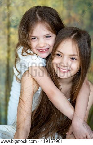 Two Little Girls With Long Hair In White Clothes Cuddle. Love Between Sisters.