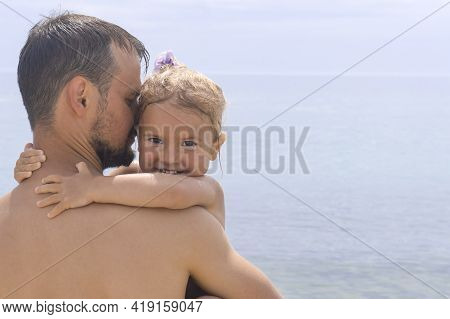 Portrait Of Child And Dad. Cute Little Caucasian Child Hugs Her Young Dad, Father Holds His Kid And