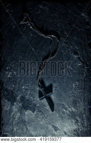 Christian cross necklace on slate background with the crucifix casting a dark shadow.