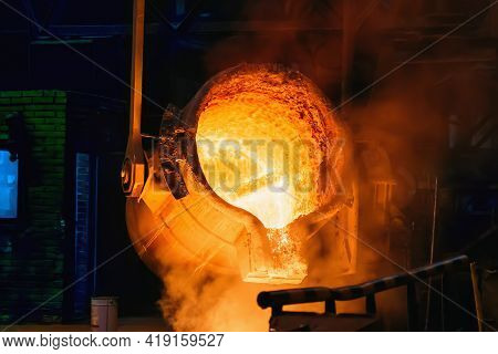 Metal Casting Process In Foundry, Molten Iron Pours From Ladle To Blast Furnace.