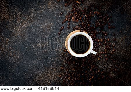 White Cup Of I Black Coffee And Coffee Beans On Dark Concrete Background. The Concept Of Hot Drinks,