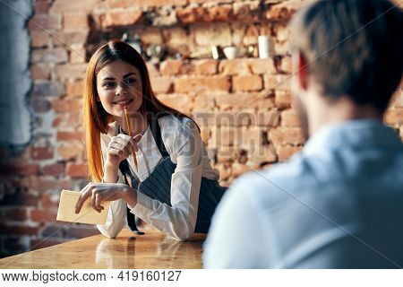 A Woman Takes An Order From A Man In A Cafe Serving A Waiter