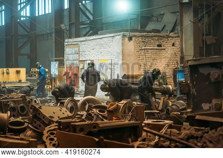 Workers In Workshop Of Metallurgical Foundry Plant Processes Large Cast Iron Parts After Casting, He