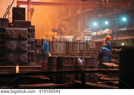 Workers In Workshop With Metal Casting Molds At Metallurgical Steel Plant, Heavy Industry Background