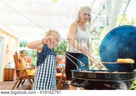 Mom and daughter at the grill doing the barbeque