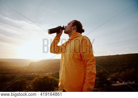 Low Angle View Of Male Athlete Drinking Water From Bottle While Resting After Run