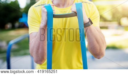 Man working out with resistance rubber bands in street, close up