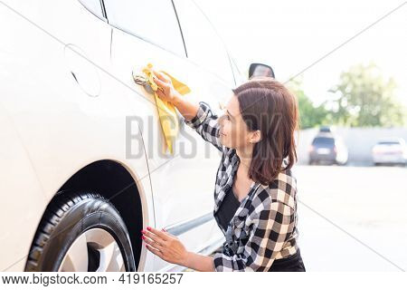 Woman wiping car door handle with rag during car wash
