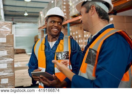African Employee Looking At His Supervisor Holding Digital Tablet In Hand At Warehouse