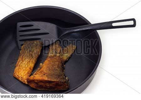 Tail Portion And Other Slice Of Fried Carp On Frying Pan With Non-stick Coating And Plastic Spatula