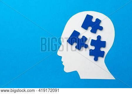 Papercut Head With Jigsaw Puzzle Pieces On Blue Background