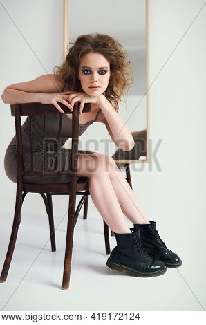 Portrait Of Pretty Strange Freaky Girl. Beautiful Extravagant Young Woman Sitting On Stool At The Mi