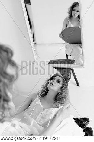 Portrait Of Attractive Strange Sad Girl. Beautiful Curious Young Woman Sitting On Chair At Mirror Wi