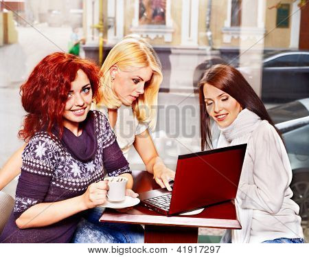 Three young women at laptop drinking coffee in a cafe.