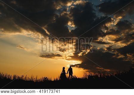 Silhouettes Of Man And Woman Walking Along The Plain On The Background Of A Beautiful Sunset Sky