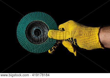 Builder Hand In Glove Keeps Or Gives Abrasive Tools Close Up On Isolated Black Background. The Idea