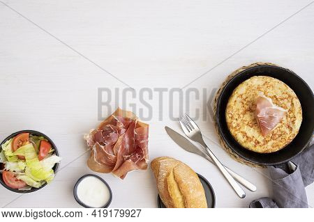 Frying Pan With Tortilla, Spanish Omelette Made With Eggs And Potatoes And Served With  Jamon,salad,