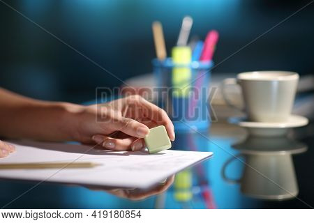 Close Up Of A Woman Hand Erasing With An Eraser In The Night At Home
