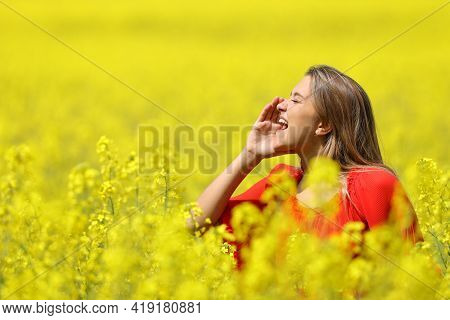 Happy Woman Shouting With Hand On Mouth In A Yellow Field In Spring Season
