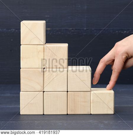 A Stack Of Wooden Cubes 6 The Person's Fingers Go Up The Steps. Business Growth Concept, Goal Achiev