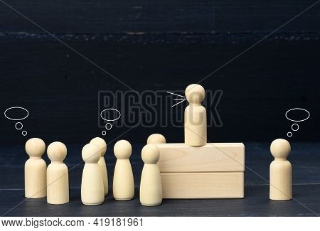 Wooden Figurines Of Men On A Blue Background. Public Speaking Concept, Leadership And Discussion. Th