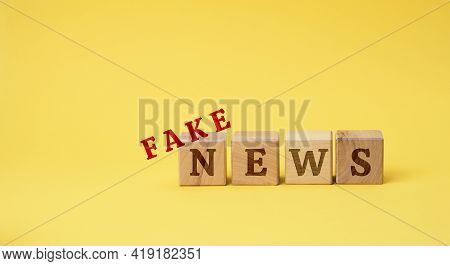 Wooden Cubes With The Inscription False News On A Yellow Background. The Concept Of Information Hygi