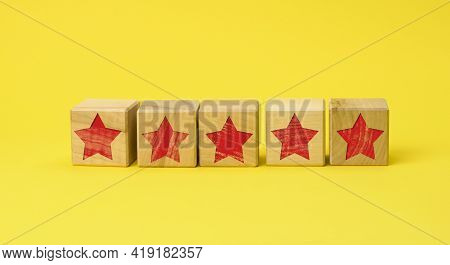 Five Wooden Cubes With A Red Star On A Yellow Background. Quality Assessment Concept, Rating. Best S