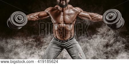 Muscular Athlete Lifts Dumbbells. Shoulder Pumping. Fitness And Bodybuilding Concept.