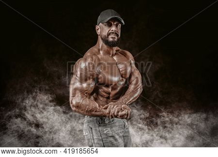 Muscular Athlete Posing In The Studio. Fitness And Classic Bodybuilding Concept.