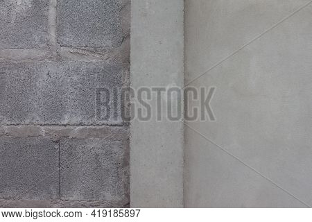 Cement Pillar Between Plastered And Unpainted Concrete Walls In The Construction Site.