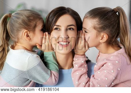people, family and concept - happy mother and two daughters gossiping at home