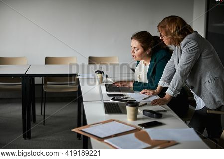 Woman Trainee Clicking On Laptop Keyboard Under Boss Supervision