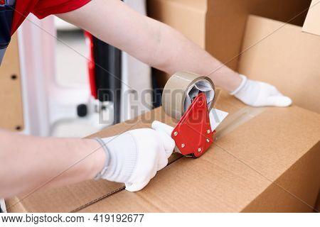 Man Packing Cardboard Box Using Dispenser Scotch Tape Closeup