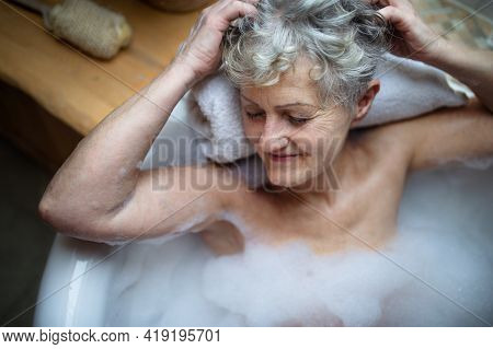 Top View Of Contented Senior Woman Lying In Bath Tub At Home, Eyes Closed.