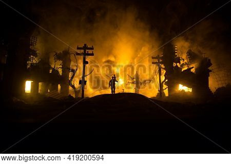 Silhouette Of A Man Carrying Injured Girl From Fire. Rescue Savior Concept. Military Officer Running