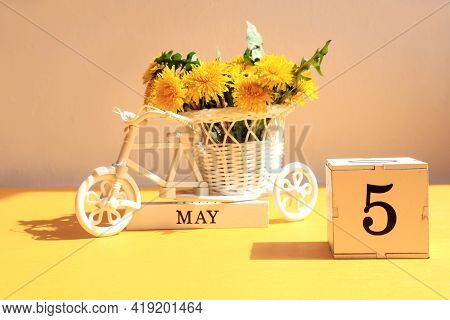 Calendar For May 5 : A Cube With The Number 5, The Name Of The Month Of May In English, A Bicycle Wi