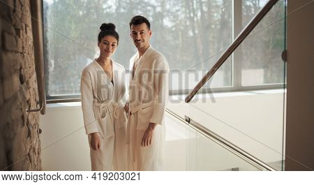 Portrait Of Young Couple In Spa Resort, Looking At Camera On Staircase.