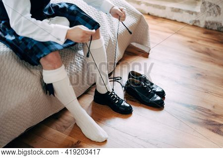Preparing For A Scottish Wedding. Man In A Kilt, Sporran And High Socks Sits On The Bed And Tie Long