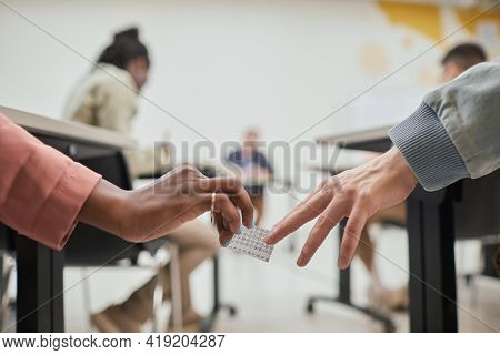 Close Up Of Two Unrecognizable Students Passing Cheat Note While Taking Exam In School, Copy Space