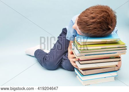 Upset Schoolboy Sitting With Pile Of School Books. Boy Sleeping On A Stack Of Textbooks Isolated On
