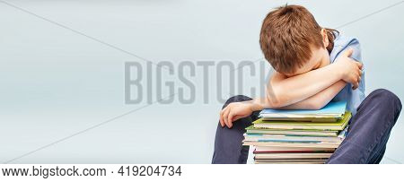 Upset Schoolboy Sitting With Pile Of School Books And Covers His Face With Hands. Boy Sleeping On A