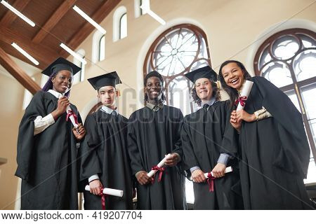 Low Angle View At Multi-ethnic Group Of Young People Wearing Graduation Robes And Looking At Camera