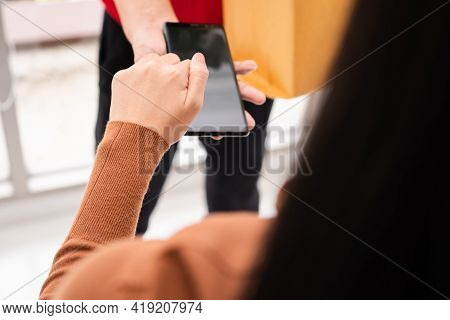 Asian Delivery Man Holding Holding A Bag Of Fresh Food For Giving To Customers And Holding Smartphon