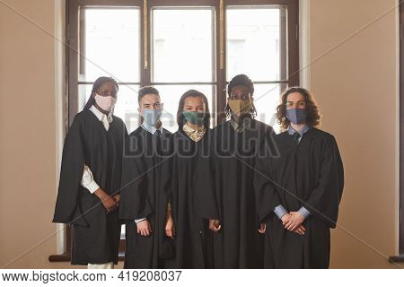Diverse Group Of Young People Wearing Masks And Black Ceremonial Robes During Graduation Ceremony In