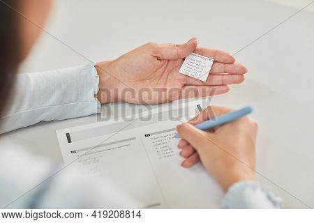 High Angle Closeup Of Unrecognizable Student Holding Cheat Note While Taking Exam In School, Copy Sp