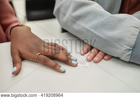 Close Up Of Two Unrecognizable Students Passing Cheat Note Sneaking White Taking Exam In School, Cop
