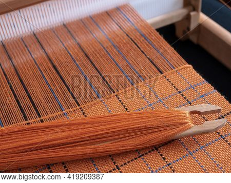 Wooden Loom With Shuttle And Woven Orange Textile With Striped Pattern. Concept Of Handloom Weaving