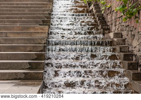 Street Fountain On The Stairs. Water Runs Down The Stairs In The Designated Area For It.